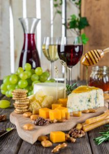 Wine decanter, one glass of white wine and one glass of red wine, board holding a variety of cheeses, one pile of crackers, grapes in the background